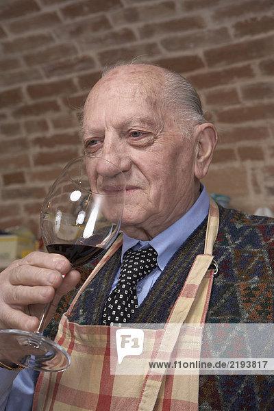 Senior Mann riecht Rotwein