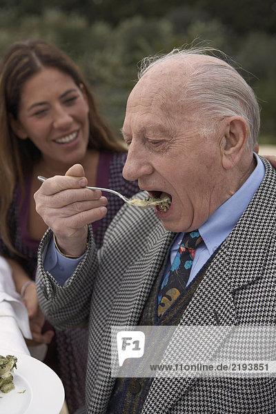 Senior Mann beim Essen am Tisch im Freien