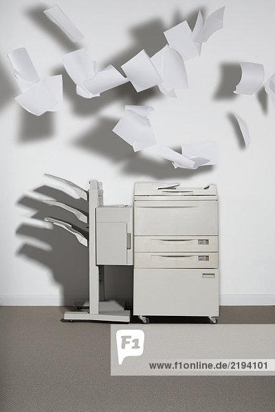 Ein Fotokopierer gegen eine weiße Wand mit herausfliegendem Papier.