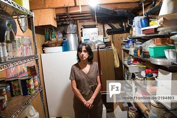 Mittleren Alters Frau posiert im Keller Storage Zimmer ihres Hauses.