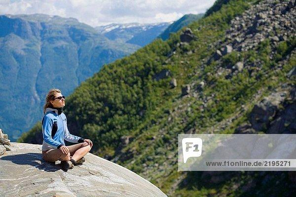 Frau sitzend auf einem Felsen. Hordaland. Norwegen.