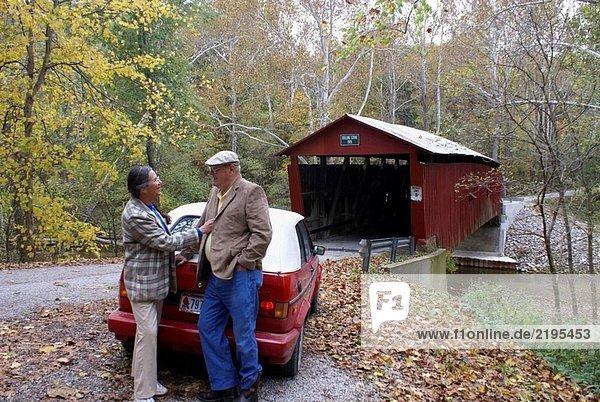 Ein ehemaliger paar anhalten  um den Herbsttag von der Rolling Stone Covered Bridge in Putnam County  Indiana  USA  genießen die Big Walnut Creek durchquert.