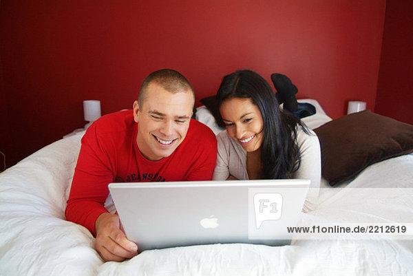 Mann und Frau beim Überprüfen des Computers