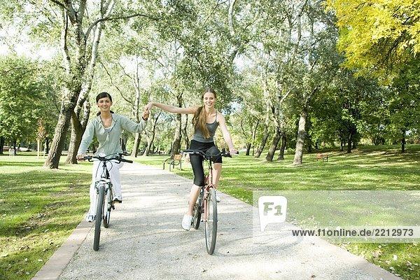 Junge Frauen fahren Fahrrad im park