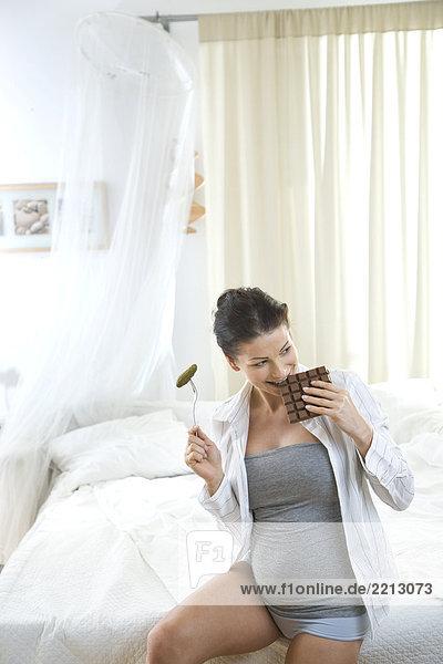 schwangere Frau mit Schokolade und pickles