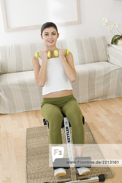 young woman training with dumbbells