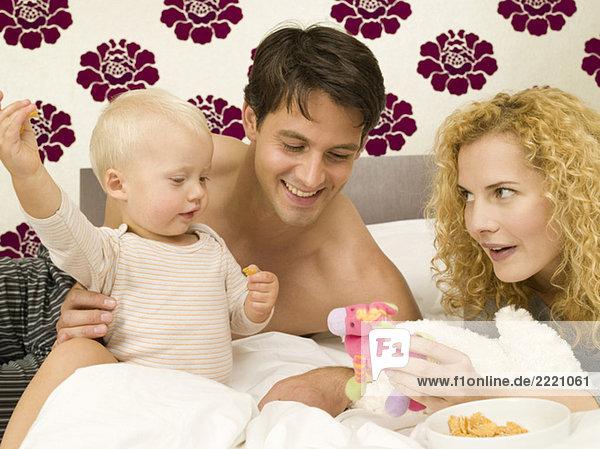 Eltern mit Kleinkind (12-24 Monate) im Schlafzimmer