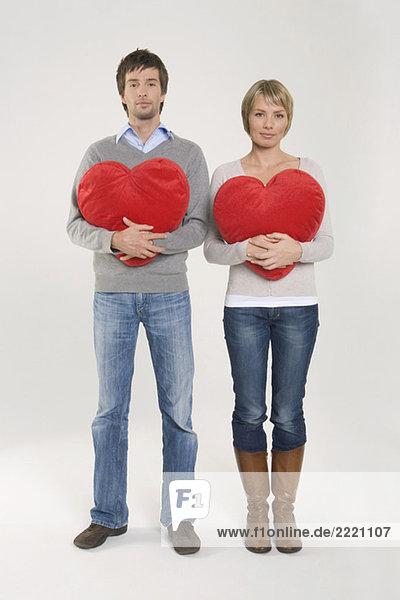 Junges Paar mit herzförmigen Kissen  Portrait