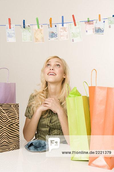 Blonde Frau trocknet Geld auf einer Wäscheleine  Portrait