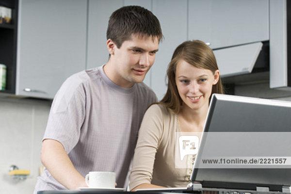 junges paar zusammensitzen in der Küche Blick auf Laptop-computer