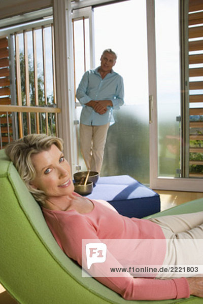 mature couple in living at home woman lying on chair