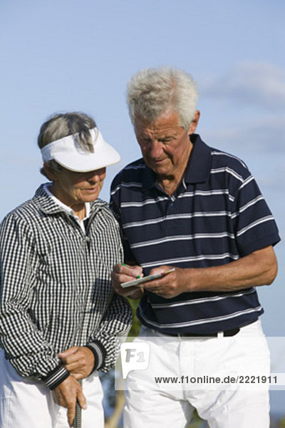 Portrait des zwei mündig Golf Spieler Menschen die Hinweise auf scorecard
