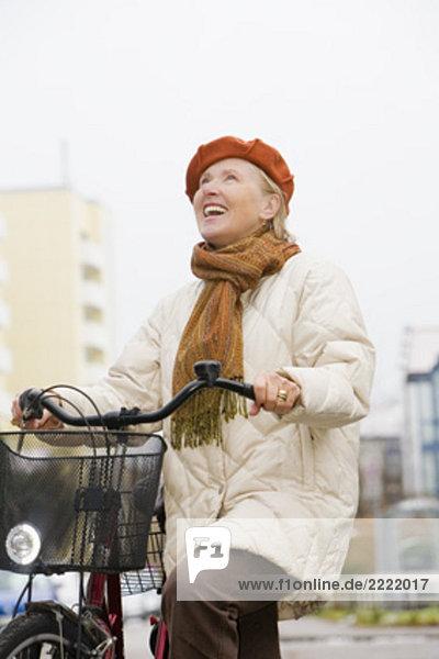 Portrait reife Frau tragen Beret und hält Fahrrad