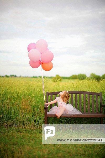 Mädchen  Alter 3 Luftballons betrachten. Mädchen, Alter 3 Luftballons betrachten.