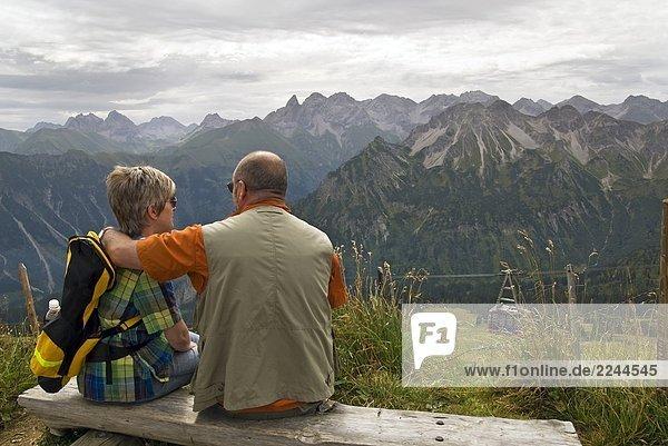 Altes Ehepaar auf einer Sitzbank in den Alpen
