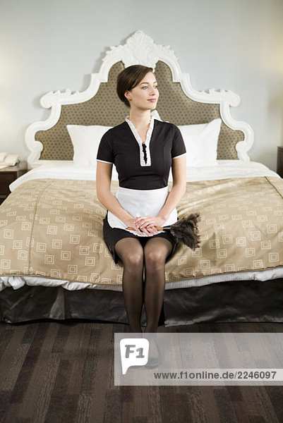 Maid sitting on Edge Bett