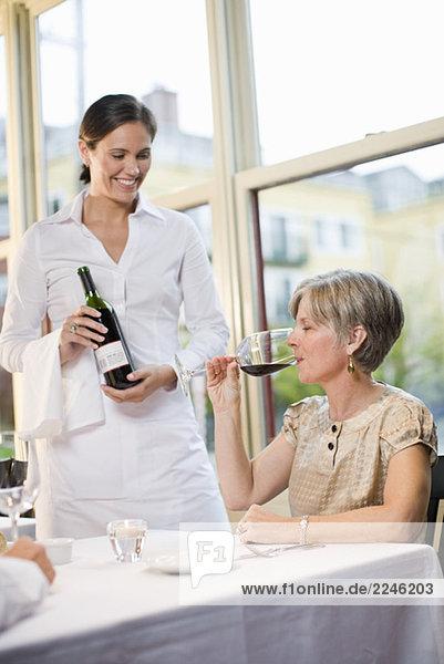 Woman tasting wine at restaurant
