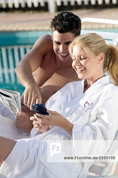 Paar am Pool mit einem Blackberry oder PDA-Telefon