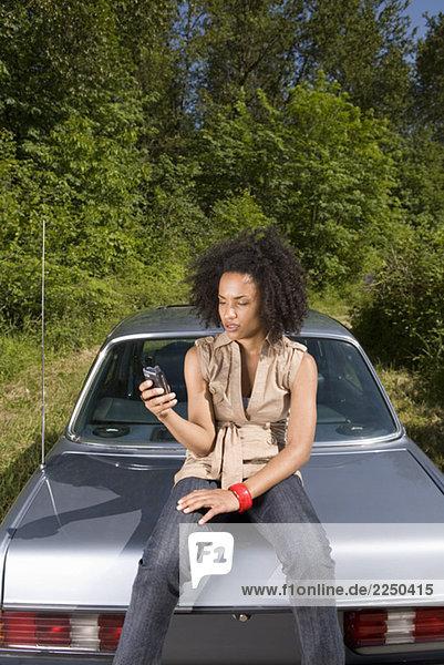 Frau mit Handy sitzen auf Kofferraum