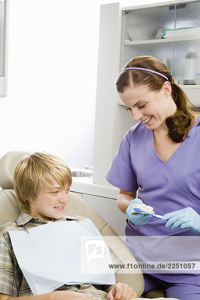 Female dentist showing patient how to brush