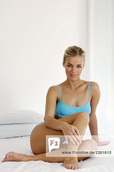 Frau sitzen auf dem Bett