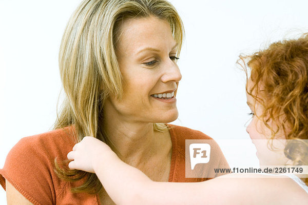 Girl touching her mother's hair  both smiling  close-up