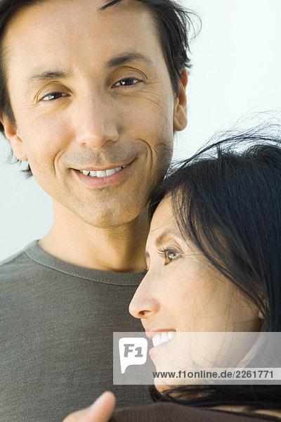 Mann lächelt in die Kamera  während die Frau ihren Kopf auf seine Brust lehnt.