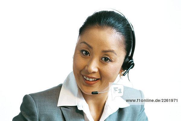 Geschäftsfrau mit Headset  lächelnd vor der Kamera  Nahaufnahme