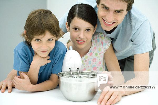 Vater und zwei Kinder beim gemeinsamen Backen  alle lächelnd vor der Kamera