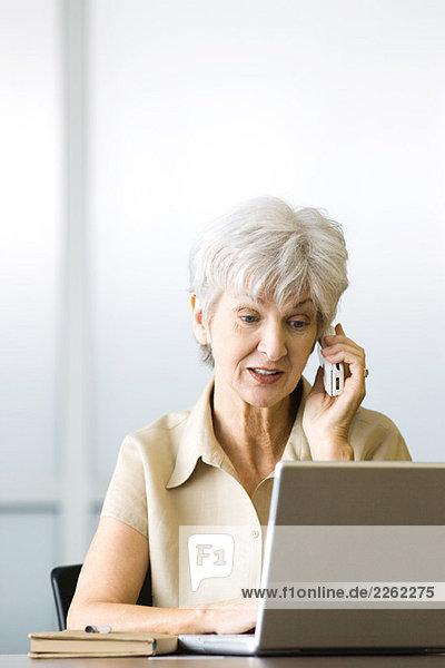Seniorenfrau mit Handy und Laptop  Blick nach unten