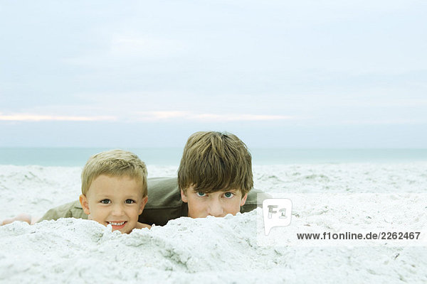 Two brothers lying on the beach together  both smiling at camera  portrait