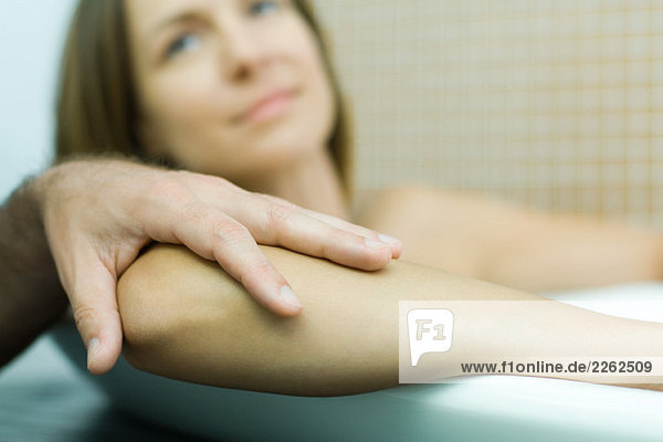 Woman in bathtub with man's hand on her elbow  focus on foreground  cropped view