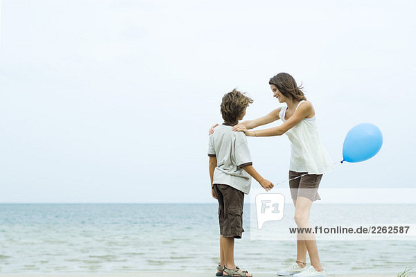 Teenagermädchen steht am Strand  Hände auf den Schultern ihres Bruders  Junge hält Ballon Teenagermädchen steht am Strand, Hände auf den Schultern ihres Bruders, Junge hält Ballon