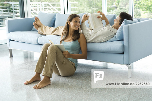 Junger Mann auf der Couch liegend  Lesebuch  Freundin auf dem Boden neben ihm sitzend