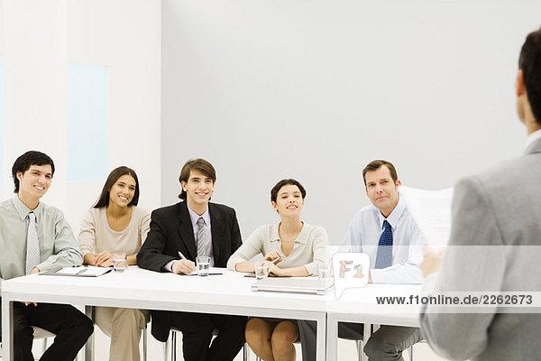 Gruppe von Profis am Tisch sitzend  lächelnd  mit Blick auf den Mann im Vordergrund.