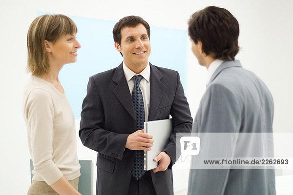 Drei Geschäftspartner stehen  reden miteinander  lächeln