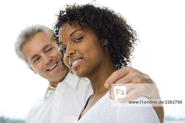 Mann mit Arm um die Schulter der Frau  Frau lächelt in die Kamera  Seitenansicht