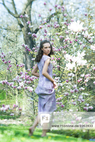 Young woman in dress walking beside flowering tree  looking over shoulder at camera