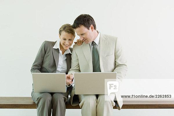 Männliche und weibliche Business associates sitzen nebeneinander  beide mit Laptops  lächelnd