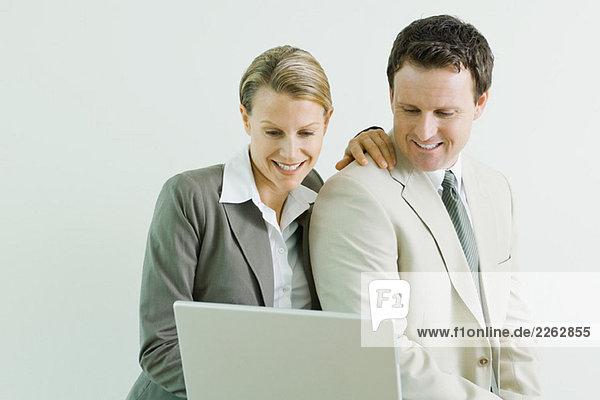 Männliche und weibliche Geschäftspartner mit Laptop-Computer zusammen  beide lächelnd