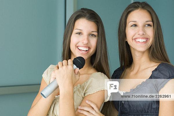 Teenage Zwillingsschwestern nebeneinander  beide Lächeln  eine hält-Mikrofon