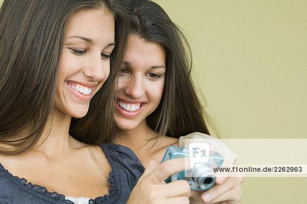 Blick in die digitale Kamera zusammen  beide lächelnd Teenager Zwillings-Schwestern