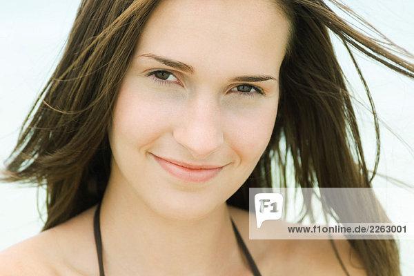 Junge Frau Lächeln in die Kamera  Haar zerzaust von Breeze  Portrait