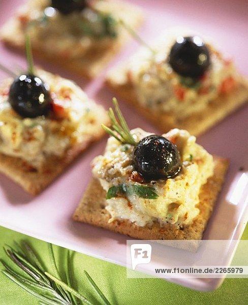 Crackers mit Auberginencreme und schwarzen Oliven