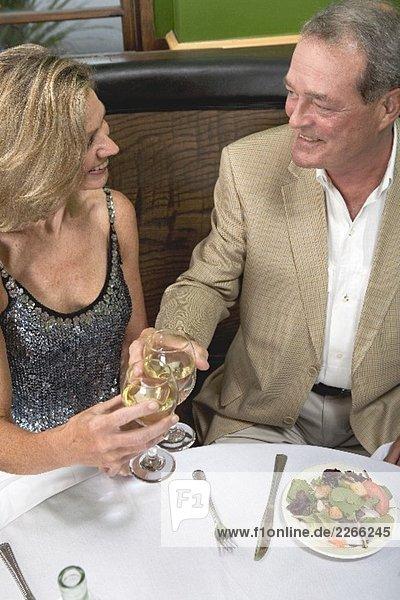 Mann und Frau im Restaurant stossen mit Wein an