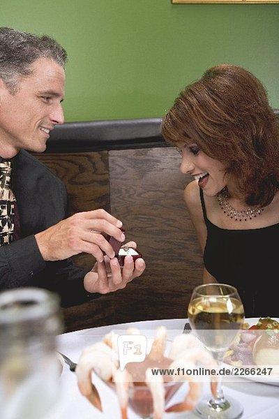 Mann schenkt Frau einen Ring im Restaurant