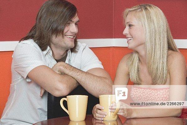 Blondes Mädchen und ein junger Mann im Café oder Restaurant