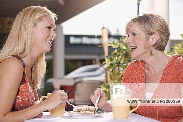 Zwei Frauen im Strassencafé teilen sich ein Stück Tiramisu