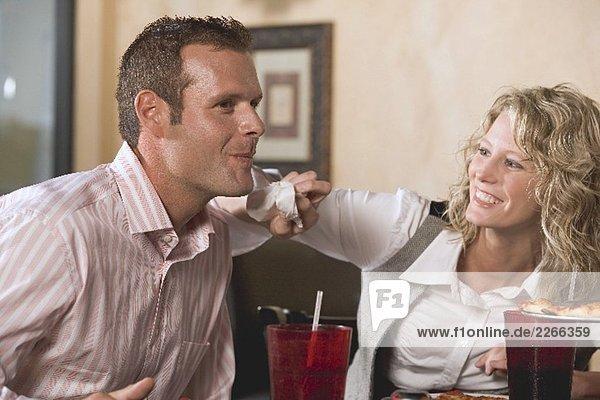 Frau im Restaurant will Mann das Kinn abtupfen