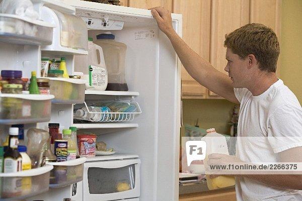 Mann im T-Shirt begutachtet den Inhalt seines Kühlschranks